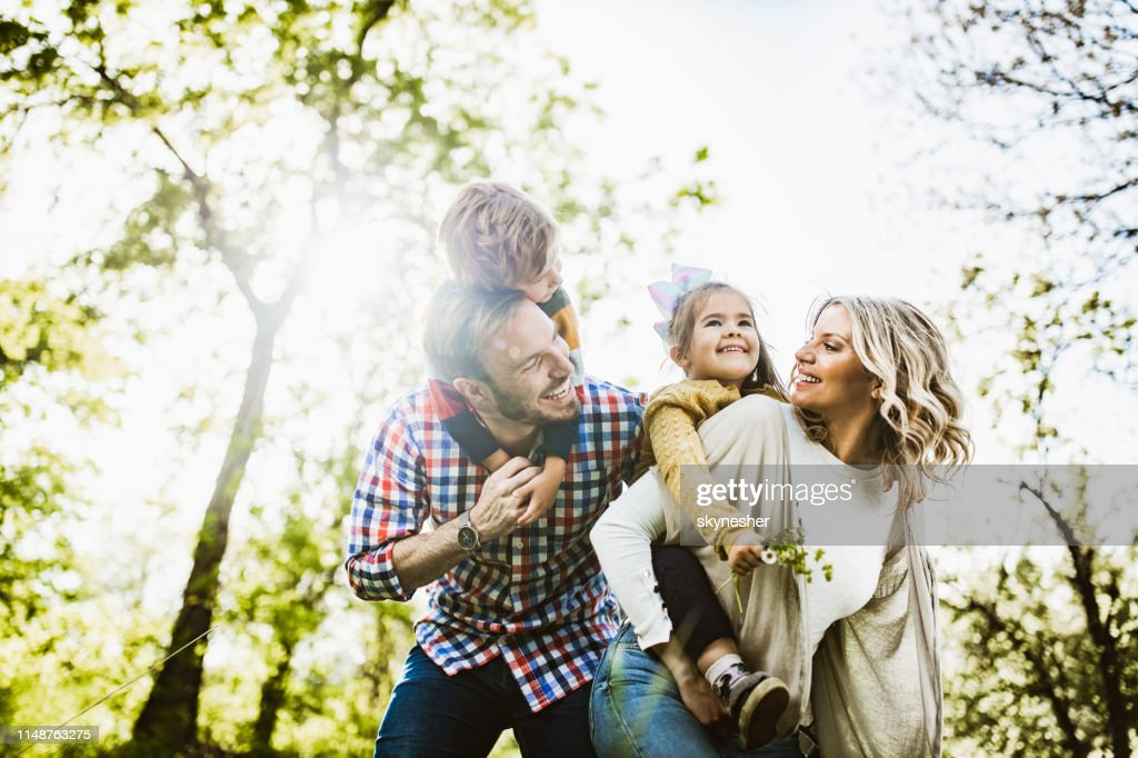 Below view of playful family having fun while piggybacking in nature. : Stock Photo