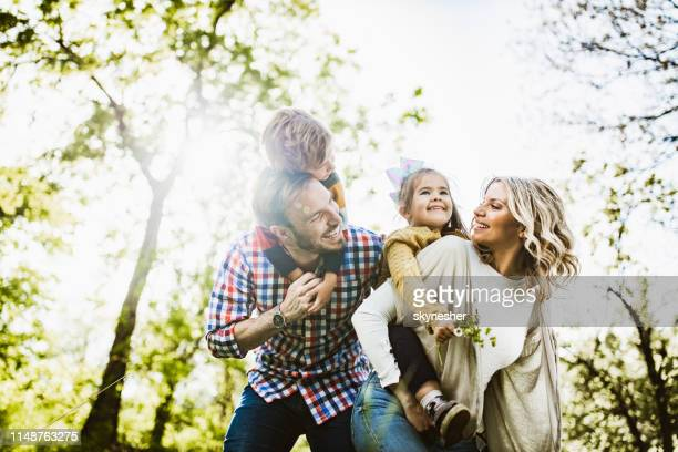 below view of playful family having fun while piggybacking in nature. - familia imagens e fotografias de stock