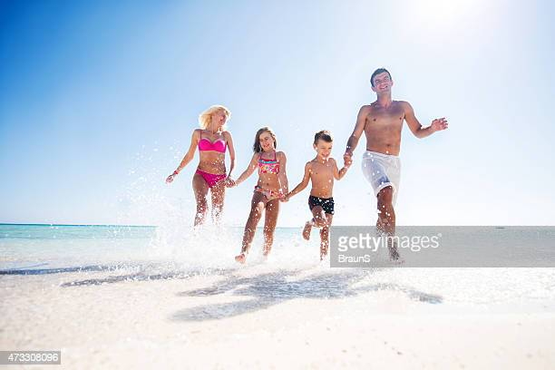 Below view of playful family running at the beach.