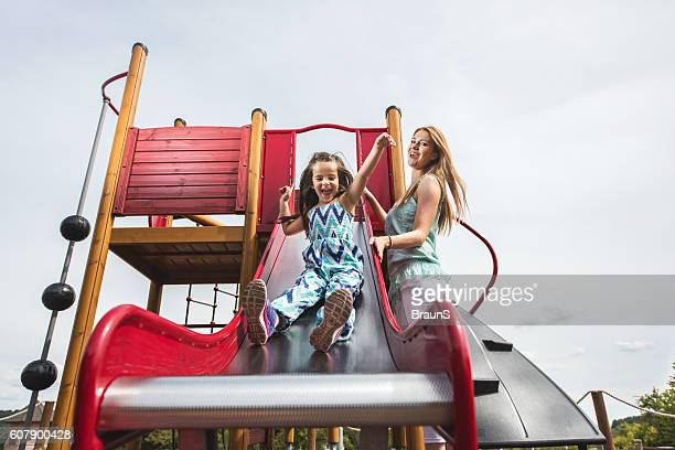 Below view of playful mother and daughter on a playground.