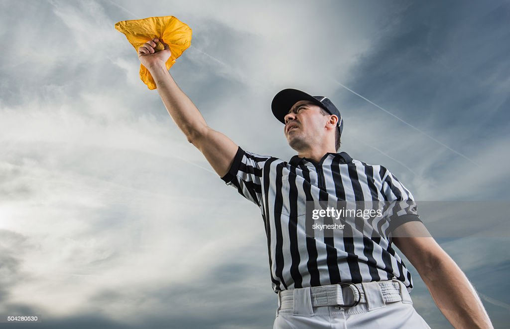 Below view of referee showing penalty against the sky. : Stock Photo
