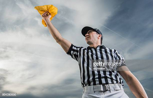 below view of referee showing penalty against the sky. - american football referee stock pictures, royalty-free photos & images