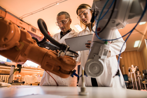 Below view of scientists cooperating while working on robotic arm in laboratory. 931633736