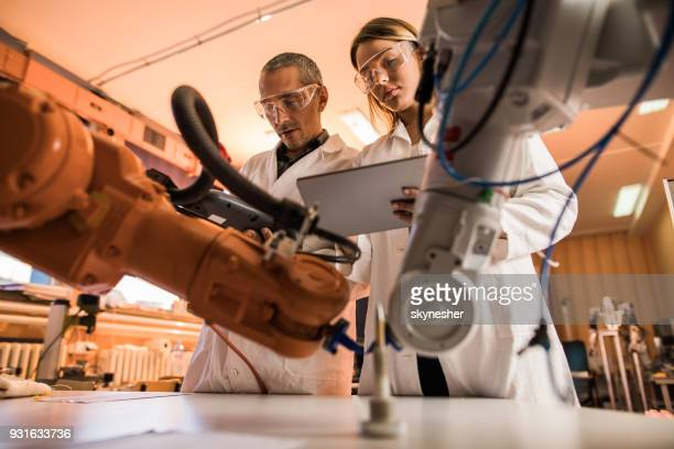 Below view of scientists cooperating while working on robotic arm in laboratory.