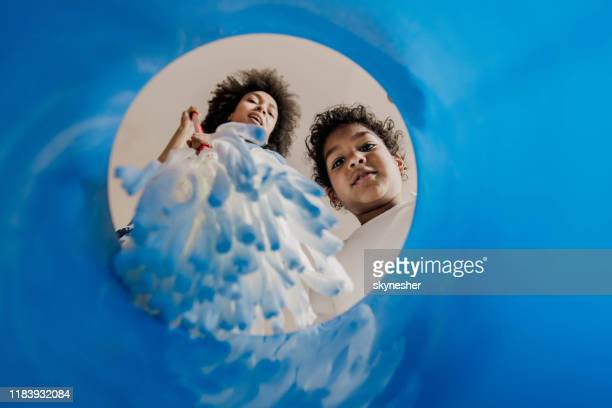 below view of single black mother and daughter dipping the mop into the bucket. - daily bucket stock pictures, royalty-free photos & images