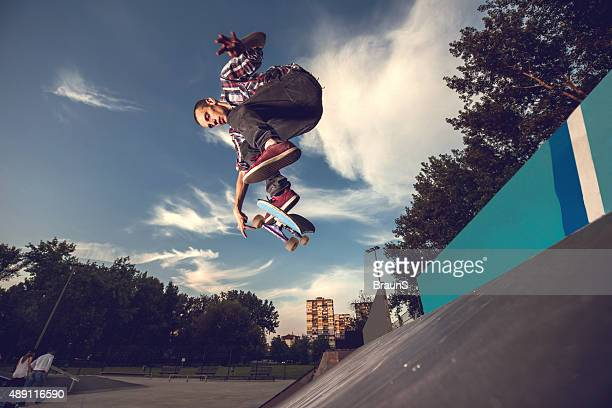 Below view of skillful skateboarder having fun at skate park.