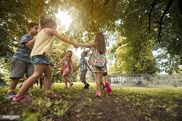 below view of small friends playing ring-around-the-rosy in the park. - dia - fotografias e filmes do acervo