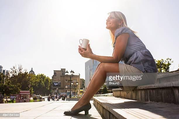 Unter Ansicht von lächelnd Geschäftsfrau auf eine Kaffeepause im Freien.