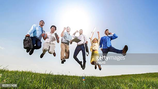 Below view of successful business people jumping in nature.