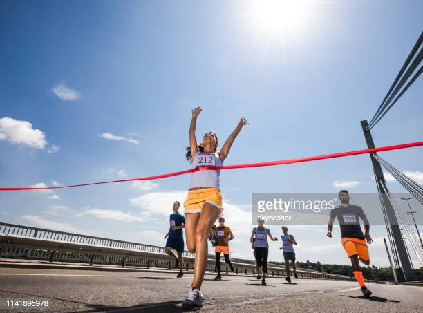 below view of successful marathon runner crossing the finish line. - finish line stock pictures, royalty-free photos & images