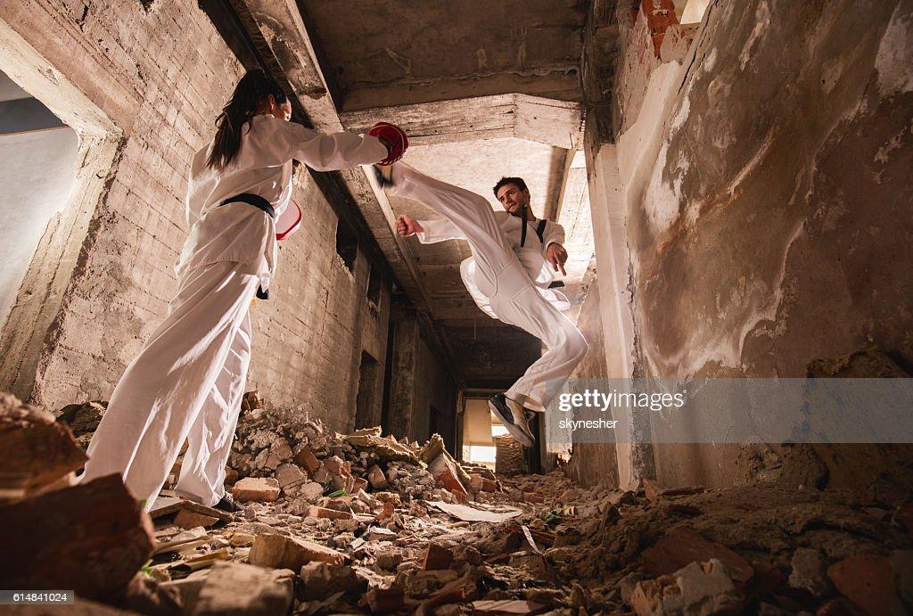 Below view of teakwondo sparring partners exercising among ruins. : Stock Photo