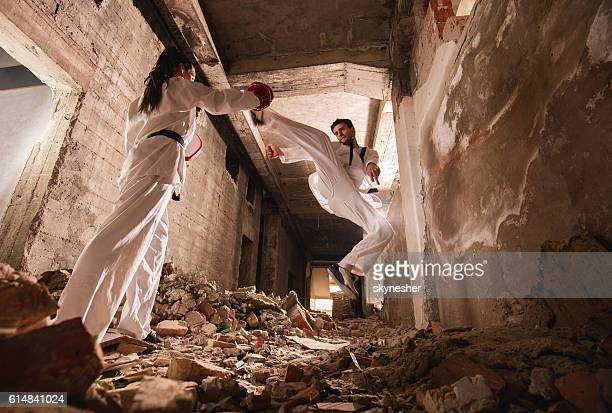 Below view of teakwondo sparring partners exercising among ruins.