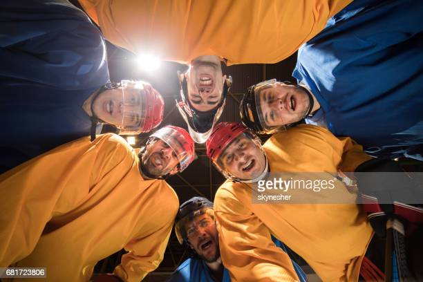 Below view of team of ice hockey players making faces and looking at camera.