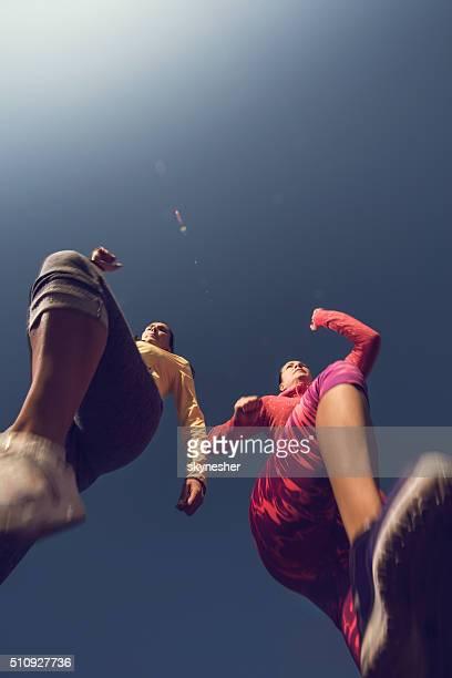 Abaixo de vista de duas mulheres movimentando-se contra o céu.
