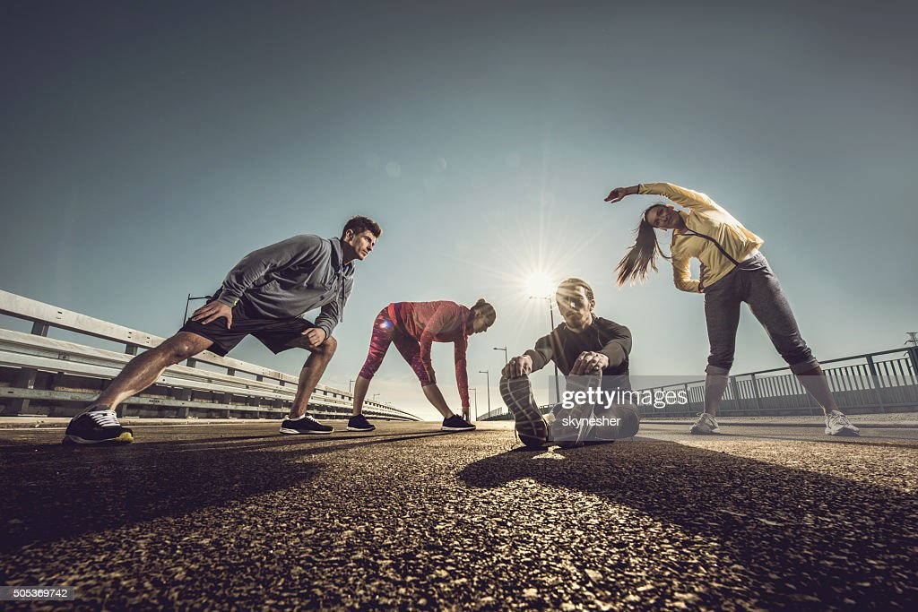 Below view of young athletes doing stretching exercises on road. : Stockfoto