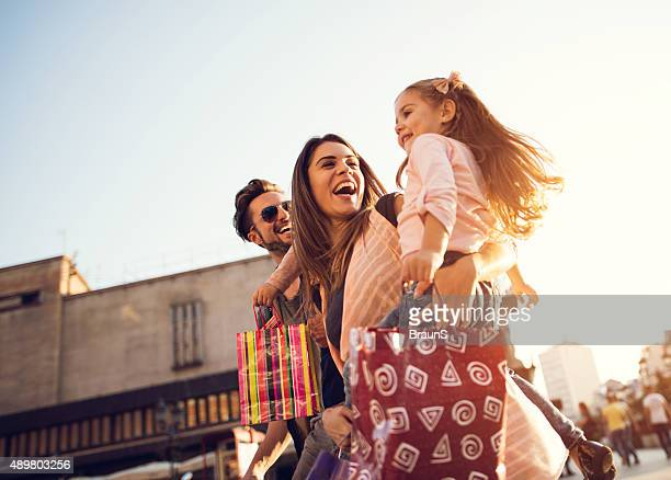 below view of young cheerful family in shopping. - winkelen stockfoto's en -beelden