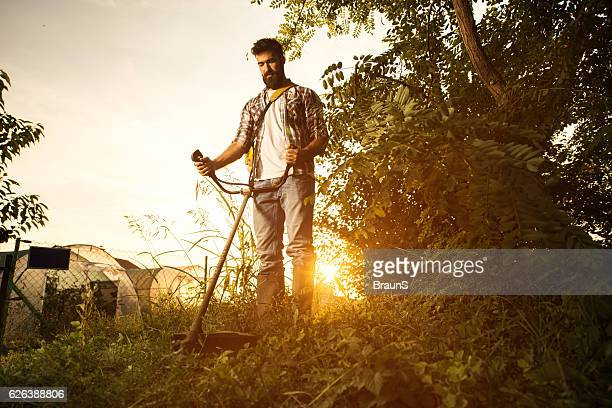 Below view of young farmer mowing the lawn at sunset.