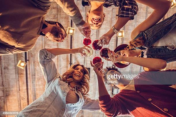Unten Blick auf junge glücklich Freunden anstoßen mit Wein.