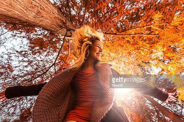 Abaixo vista de jovem feliz Mulher a divertir-se no Outono.