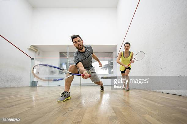 below view of young man and woman playing squash. - squash sport stock pictures, royalty-free photos & images