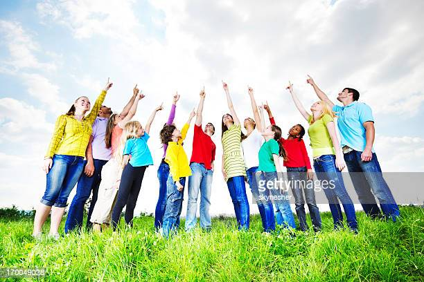 below view of young people pointing at the sky. - wijzen handgebaar stockfoto's en -beelden