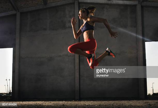 below view of young sportswoman jumping high up during cross training. - crossfit stock pictures, royalty-free photos & images