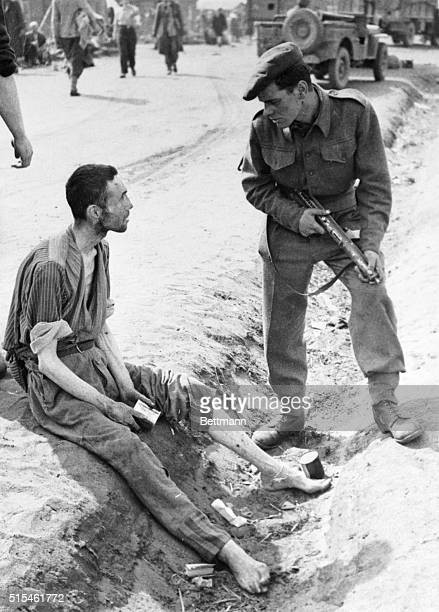 A British soldier listens to the story of an inmate of the horror camp at Belsen