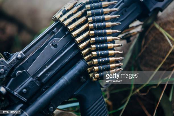 a belt of blank training bullet rounds resting on top of an light machine gun - gunman stock pictures, royalty-free photos & images