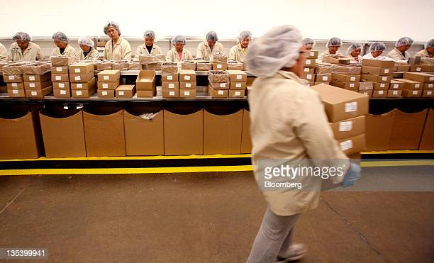 A belt stocker carries bulk boxes of chocolate to packers at the See's Candies Inc packing facility in South San Francisco California US on Thursday...