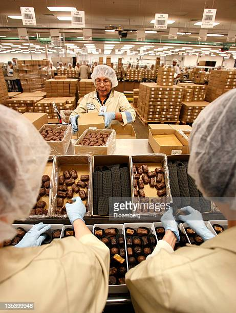 Belt stockers pack boxes of chocolates at the See's Candies Inc packing facility in South San Francisco California US on Thursday Dec 8 2011 Brad...