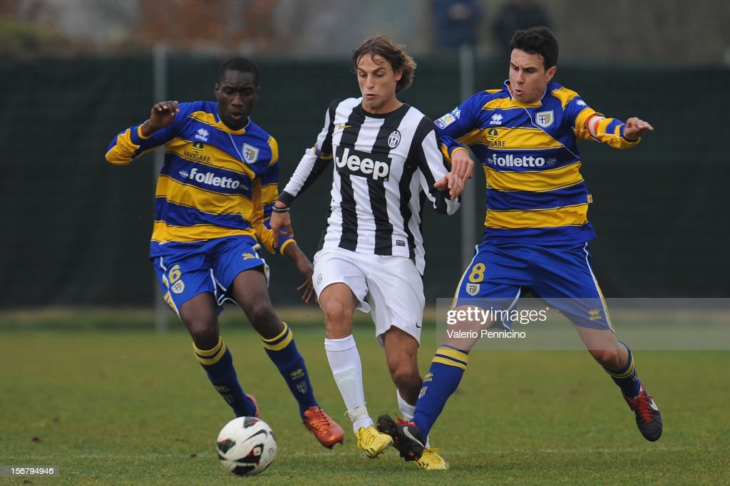 Beltrame (C) of Juventus FC is challenged by Sall (L) and Moroni (R) of FC Parma during the Juvenile match between Juventus FC and FC Parma at Juventus Center Vinovo on November 21, 2012 in Vinovo, Italy.
