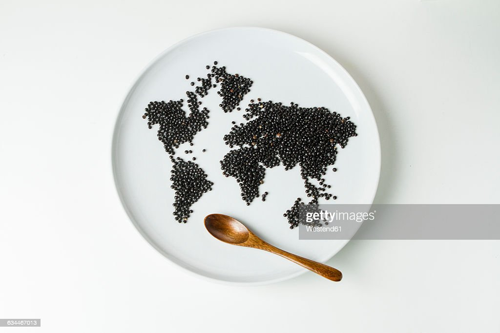 Beluga lentils on plate shaped like a world map with wooden spoon : Stock Photo