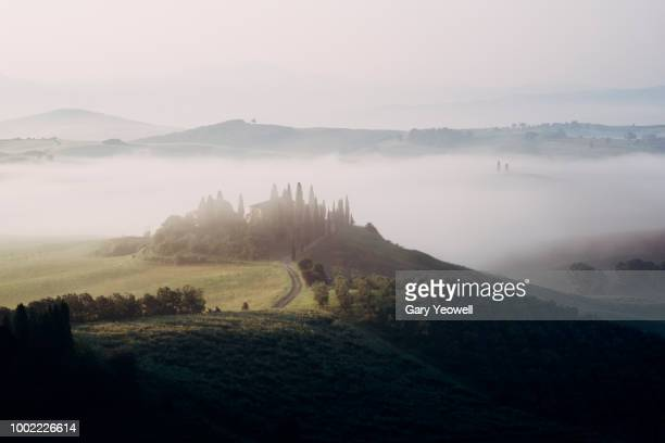 belvedere farmhouse in rolling tuscany landscape covered in mist - yeowell stock pictures, royalty-free photos & images