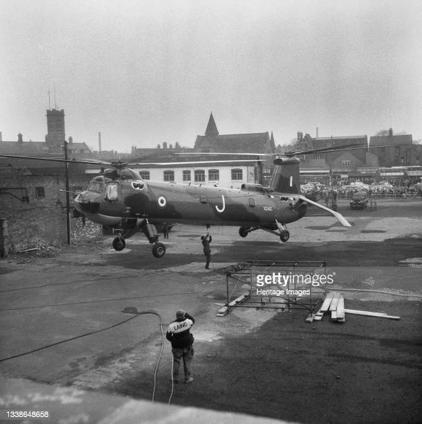 Belvedere helicopter hovering above tarmac just to the north of Coventry Cathedral, while a serviceman is attaching a hoist to the underside of the...