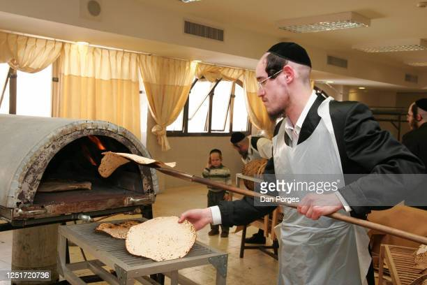 Belz Hasidic man uses a long stick with a tray in the end of it to take the ready matzah shmura out of the oven where it was baked for only ten...