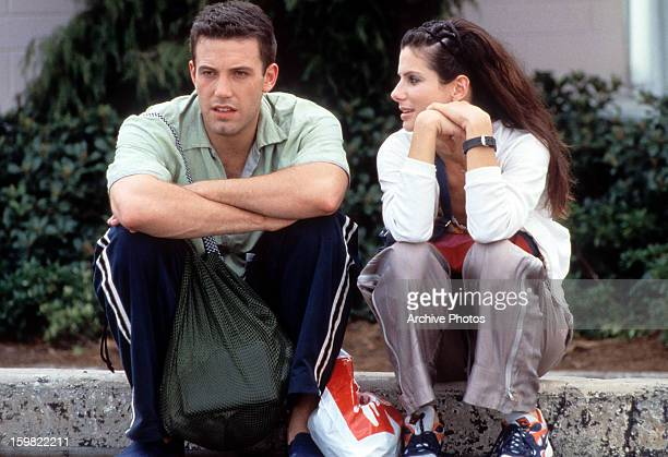 Ben Affleck sits on a sidewalk with Sandra Bullock in a scene from the film 'Forces Of Nature' 1999