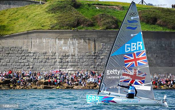 Ben Ainslie of Great Britain celebrates winning gold in the Finn Class Medal race as fans cheer him on from the Nothe at Weymouth Harbour on August 5...