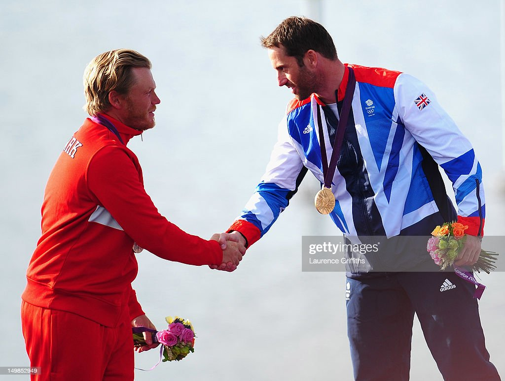 Ben Ainslie of Great Britain is congratulated on winning gold by Jonas Hogh-Christensen of Denmark after the Finn Class Medal race at Weymouth Harbour on August 5, 2012 in Weymouth, England.