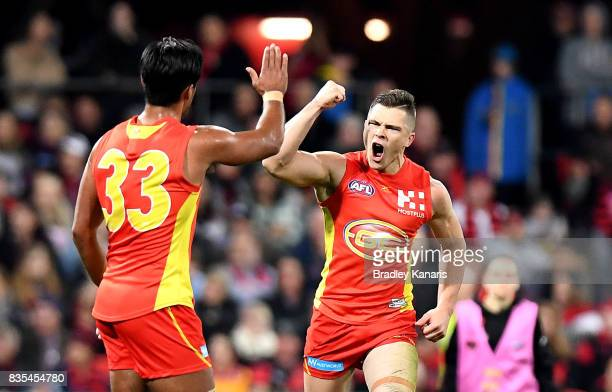 Ben Ainsworth of the Suns celebrates after kicking a goal during the round 22 AFL match between the Gold Coast Suns and the Essendon Bombers at...
