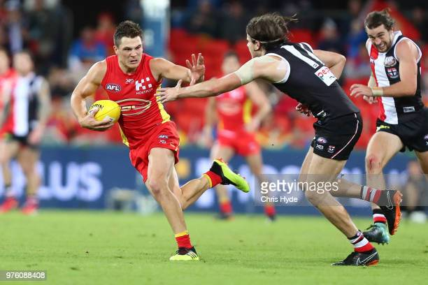 Ben Ainsworth of the Suns runs the ball during the round 13 AFL match between the Gold Coast Suns and the St Kilda Saints at Metricon Stadium on June...