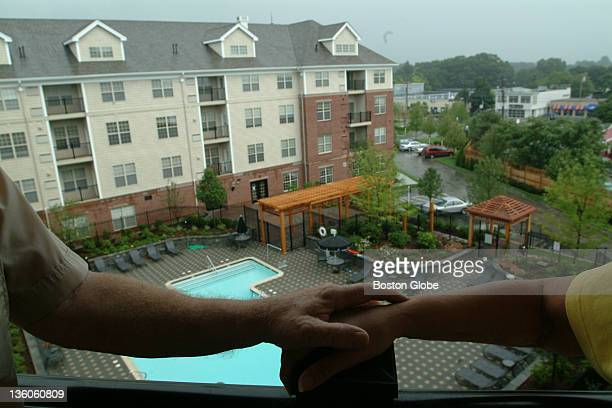 Ben and Phyllis Evans hold hands on the balcony of their rental apartment at the Avalon at Newton Highlands a luxury rental complex on Needham Street...
