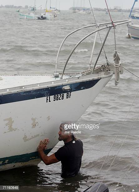 Ben Appel tries to push one of four sailboats off shore after they crashed ashore when Tropical Storm Alberto broke them from their moorings as it...