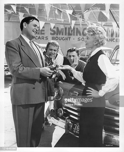 Ben Astar counts money as he hands it over to Barbara Ruick in a scene from the film 'Affairs Of Dobie Gillis' 1953