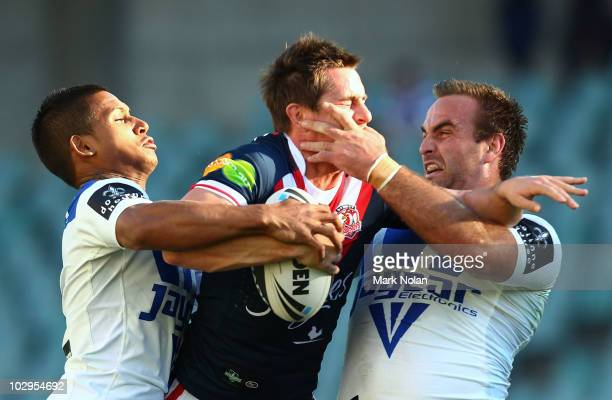 Ben Barba and Ryan Tandy of the Bulldogs tackle Mitchell Pearce of the Roosters contest a high ball during the round 19 NRL match between the Sydney...