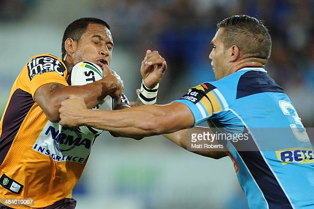 Ben Barba of the Broncos is tackled by Maurice Blair of the Titans during the round 6 NRL match between the Gold Coast Titans and the Brisbane...