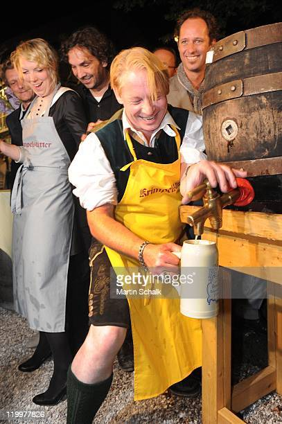 Ben Becker broaches the beer barrel at the launch party at Krimpelstaetter tavern after the 'Jedermann' premiere during the Salzburg Festival on July...
