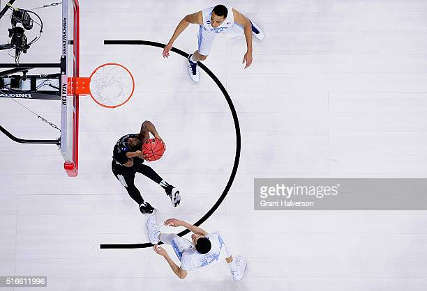 Ben Bentil of the Providence Friars drives between defenders Brice Johnson and Justin Jackson of the North Carolina Tar Heels during the second round...