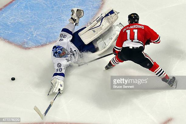 Ben Bishop of the Tampa Bay Lightning dives for the puck against Andrew Desjardins of the Chicago Blackhawks during the second period in Game Six of...