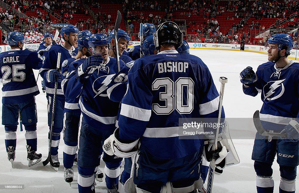 Ben Bishop #30 of the Tampa Bay Lightning is congratulated by his teammates after a shutout victory over the Carolina Hurricanes during their NHL game at PNC Arena on November 1, 2013 in Raleigh, North Carolina.The Lightning defeated the Hurricanes 3-0.