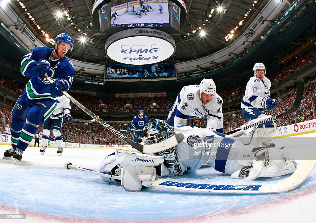 Ben Bishop #30 of the Tampa Bay Lightning makes a save as Henrik Sedin #33 of the Vancouver Canucks looks for a rebound during their NHL game at Rogers Arena October 18, 2014 in Vancouver, British Columbia, Canada.